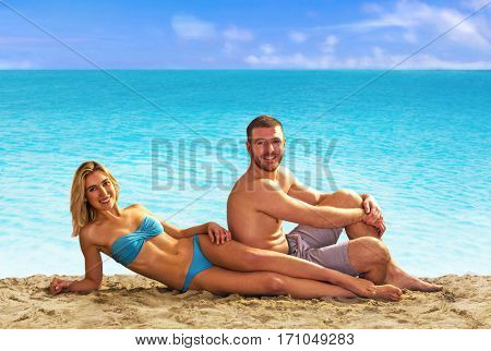 Young couple lying down on sand sunbathing on tropical beach.