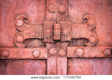 The hinge on an old metal gate red color. Close-up