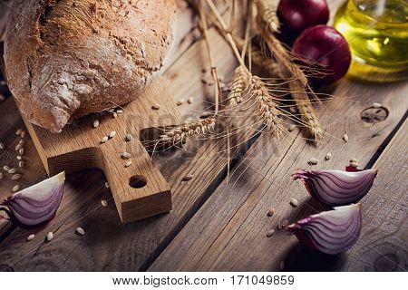 Fresh multigrain crusty bread onion and wheat ears on a rustic wooden table. Bakery and grocery food store concept.