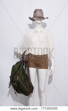 female clothing with hat and black bag on mannequin-wooden background