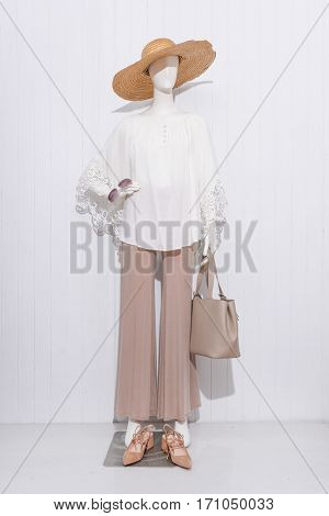 female clothing with hat and bag, sunglasses on mannequin