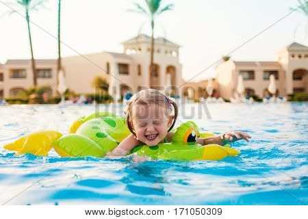 Portrait of cute happy little girl having fun in swimming pool, floating with inflatable ring. Active summer vacation on the beach.