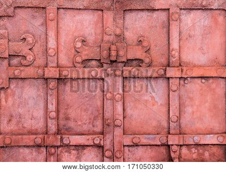 The hinge on an old metal gate red color