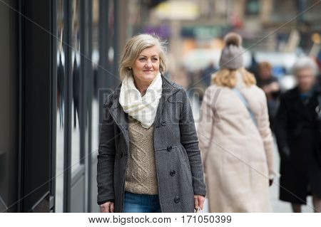 Beautiful senior woman in black coat and woolen scarf on a walk in historical centre of the city of Vienna, Austria. Winter.