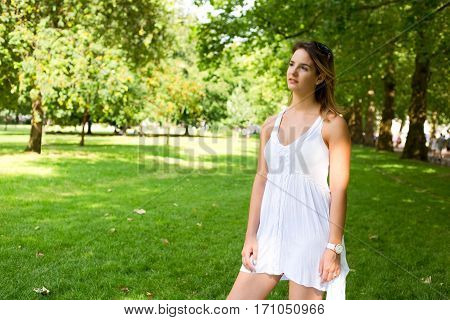 girl in the park wearing a summery white dress