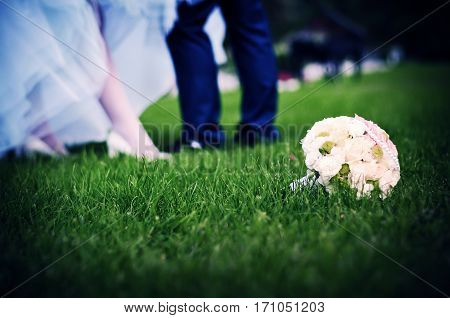 Young couple standing on the grass. In the foreground is a bridal bouquet