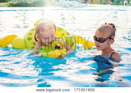 Portrait of cute happy little girls having fun in swimming pool, floating with inflatable ring. Active summer vacation on the beach.