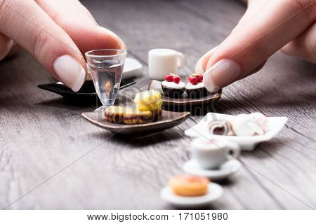 Woman arranging a miniature tea set and cookies with tiny iced cakes parfait glass and cups of tea on a rustic wood table