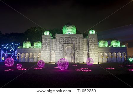 DUBAI UAE - DEC 6 2016: Arabian palace at the Dubai Garden Glow family theme park illuminated at night. United Arab Emirates Middle East
