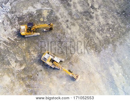Aerial view of a working excavator in the mine. Industrial background on mining theme. Heavy industry from above.