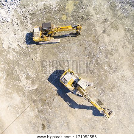 Aerial view of a working excavators on a construction site. Industrial background and heavy industry from above.