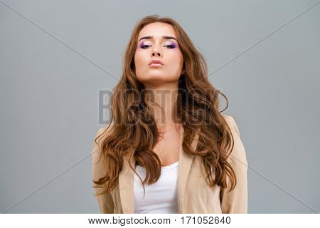Haughty eyes on top. Beautiful brunette woman face close up portrait studio isolated on gray background