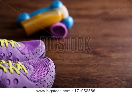 Fitness gym equipment. Sneakers, dumbbells with towel. Fresh orange juice drink. Workout footwear. Sport trainers on grunge rustic wood background.