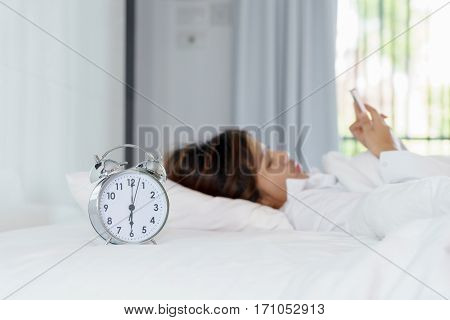 Young woman using smart phone on bed when waking up in the morning