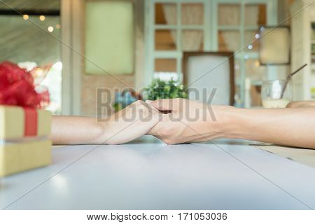 A couple holding hands each other in restaurant with a golden gift box with red ribbon