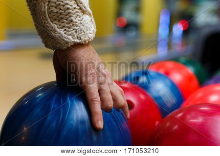 Male hand taking ball from bowling machine, closeup. Man plays game