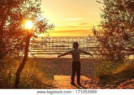 boy walking on the beach in the sand at sunset