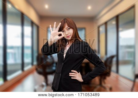 Happy business woman making an ok or okay sign in meeting room