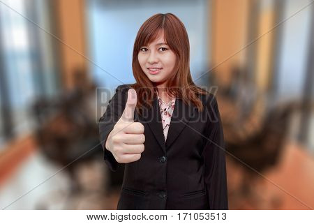 Smiling businesswoman holding thumps up in meeting room - feel good business concept.