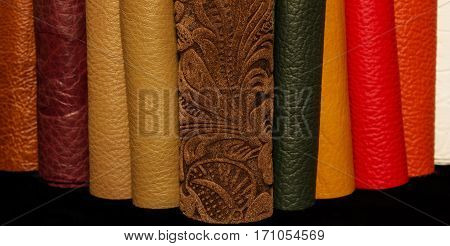 Leather rolls of different colors and textures, staked together vertically. Isolated on a black background.