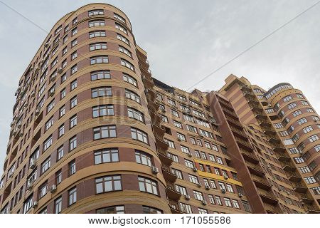 Bending of a modern residential building on a background of the sky. Architecture