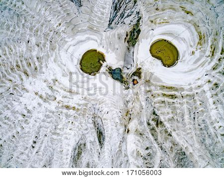 abstract patterns on the ground from water streams resembling owl, aerial shoot, top view