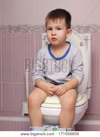 Little boy sitting in the bathroom on the toilet room