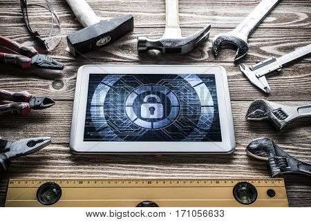 Tablet pc with security concept on screen and industrial tools around