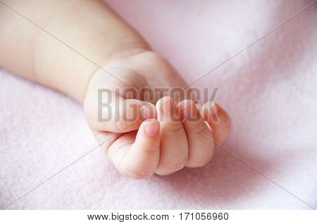 rączka małej dziewczynki śpiącej na różowym kocyku