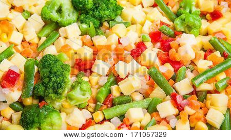 A cocktail of frozen chopped vegetables close-up as background