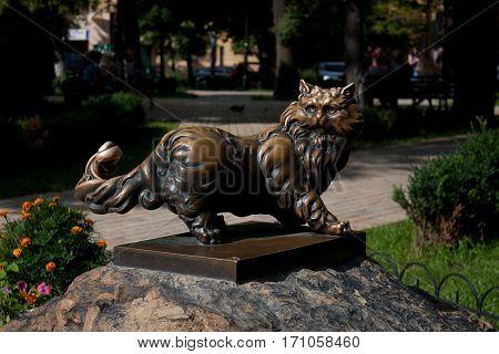 bronze cat in glasses on a stone pedestal