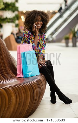 Beautiful afro-american girl talking on the phone and smiling in a center of the shopping mall.