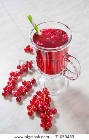 A cup of red currant aerated lemonade with green straw
