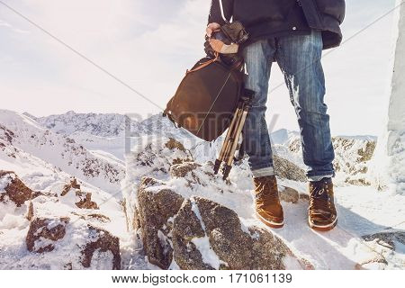 Photographer traveler on a mountain top with equipment in hands. Winter fashion