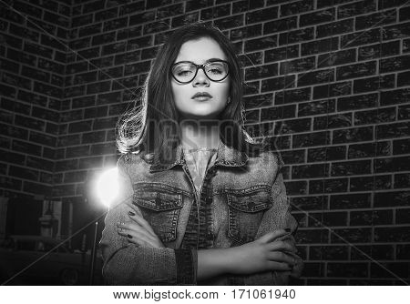 Black and white portrait of beautiful teen girl, wearing glasses, with arrogant expression and hands crossed