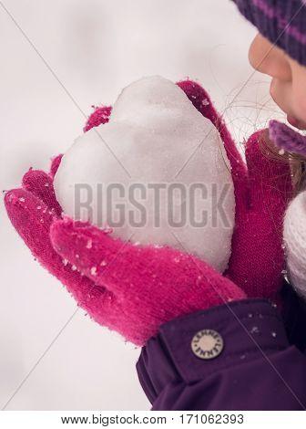Girl lovingly gives icy heart. Happy Valentine's day.