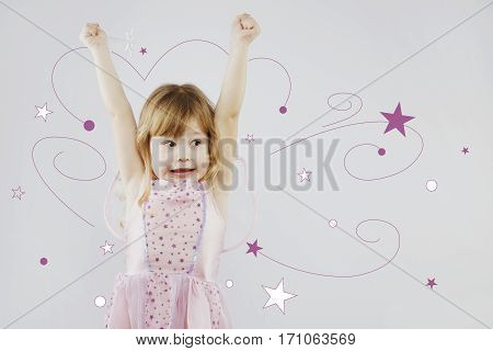 Cheerful little girl, with curly blond hair, wearing on pink dress and fairy wings, puts her hands up with magic stick, on gray background with painted purple and white stars, in studio, waist up