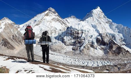 Himalayas mountains view of Mount Everest Lhotse and Nuptse from Pumo Ri base camp with two tourists on the way to mount everest base camp Sagarmatha national park Khumbu valley himalaya Nepal