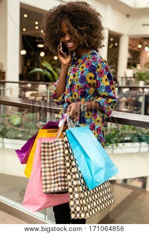 Smiled afro-american woman talking on the phone and holding coloured shopping bags in a shopping mall.