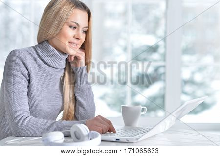 Portrait of a young beautiful blonde woman using laptop