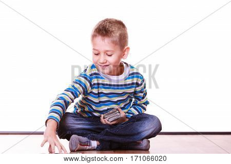 Free time fun and hobby. Little boy play indoors sit on floor and play collect cards.