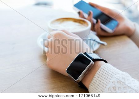 Woman's hands with black manicure and smart watch on hand, holding mobile phone, cup of coffee on light wooden table, mock up, close up.
