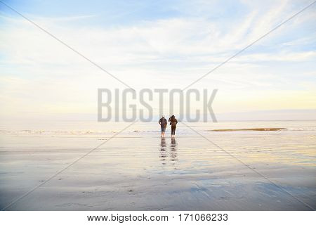 Couple, Man And Woman Standing On Ocean Beach On Sunset