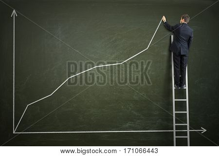 Successful Businessman Is Standing On Ladder And Drawing Growing