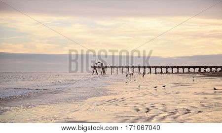 Ocean pier jetty at spectacular sunset. People walking on beach. Peaceful scene calming waves pastel cloudy sky coast. Soft light