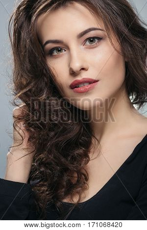 Beautiful brunette woman with long curly hair and big eyes wearing black shirt looking at camera, holding hand near hair, gray studio background, make up model.