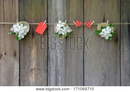 Cute ornament of blooming apple trees and red hearts in polka dots handmade. Declaration of love. Rustic style. Celebratory background. Wedding. Valentine's Day. Mothers Day. Wooden plank old background.