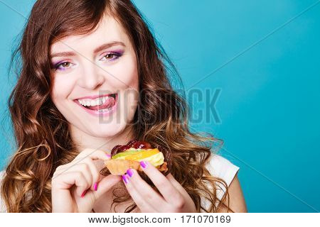 Sweet food sugar make us happy. Cute young woman colorful makeup nails holds fruit cake in hand blue background