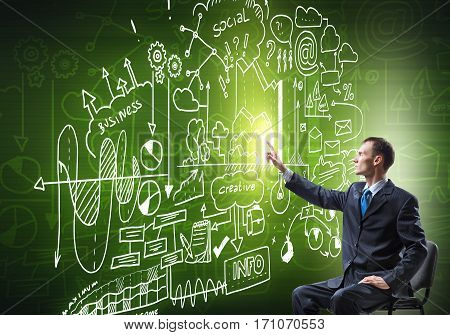 Businessman sitting in chair and sketching business strategy