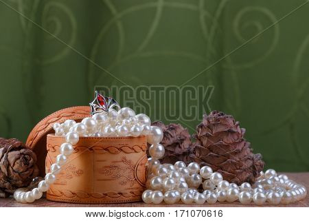 small birch bark casket with pearl beads and cedar cones on green fabric background